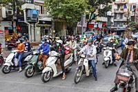 Motor cycles travelling through Hanoi city centre, Vietnam, Asia.