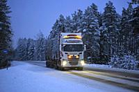 Salo, Finland - January 25, 2019: Scania R520 logging truck of E Nousiainen lights up rural highway in the blue hour of winter dusk.