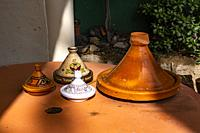 Decorated, earthenware pots on a table in a garden.
