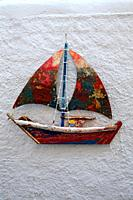Toy sailboat hanging on a white wall, Oia, Santorin, Greece, Europe.