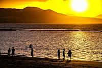 Children playing on the beach during sunset at the coastline of Las Palmas de Gran Canaria, Canary Islands.