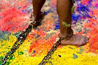 A chained Catholic devotee, with cactus spines stuck to his leg, walks on a colorful sawdust carpet during the Holy week penitential procession in Atl...