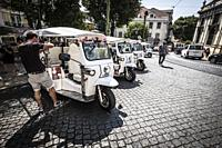 Tourists enjoy a ride in a tuk tuk, three wheeled vehicle in the center of Lisbon, Portugal.