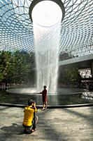 Singapore, Republic of Singapore, Asia - A man is taking a picture of his wife in front of the indoor waterfall inside the new Jewel Terminal at Chang...