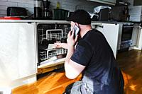 Stockholm, Sweden An installer or contractor installs a dishwasher in an apartment kitchen.