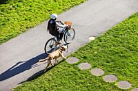 Young woman on her bicycle walking her dog in the village of Steveston British Columbia Canada
