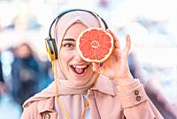 Portrait of Beautiful Muslim woman in headscarf and fashionable modern trendy with headphones holds half of citrus fruit in hand, covering her eye.