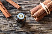 A dark bottle of essential oil with cinnamon sticks.