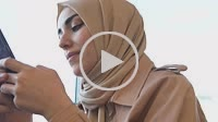 Beautiful Muslim woman in headscarf and fashionable modern trendy clothes uses and text smart phone.Modern Muslim woman lifestyle or business concept