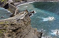Stone bridge and narrow cliff trail above the Bay of Biscaya on the islet of San Juan de Gaztelugatxe, Bakio, Costa Vasca, Bay of Biscay, Basque Count...