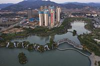 """Kunming, China â. """" May 17 ,2019: Aerial 360 degree view of the Kunming Waterfall Park at sunset, one of the largest manamde waterfalls in the world."""