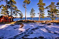 Snow and ice with traditional falu red timber cottage on the Baltic Sea coast, Sandhamn Island, Stockholm archipelago, Sweden, Scandinavia. Sandhamn i...