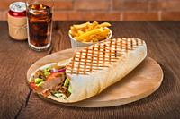 Gyros pita sandwich with french fries and cola on wooden background. For fast food restaurant design or fast food menu.