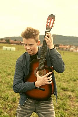 male teenager with guitar outdoors at countryside, in Waakirchen, Bavaria, Germany