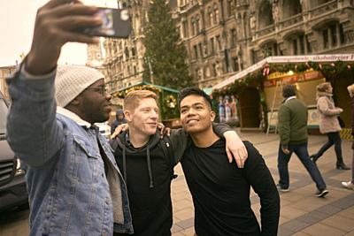 young men taking selfie in front of Neues Rathaus and Christmas market at Marienplatz in Munich, Germany.