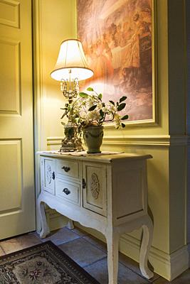 Antique wooden console with lamp and flower vase in the kitchen entryway inside a 2006 reproduction of a 16th century Renaissance castle style residen...