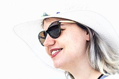 Portrait of a smiling girl with summer hat and sun glasses.