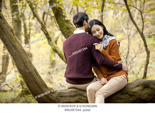 Young romantic couple sitting on a branch and hugging each other with their eyes closed in forest in fall