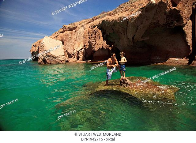 a father and son standing on a rock in the ocean at los islotes national marine park espiritu santo island, la paz baja california mexico