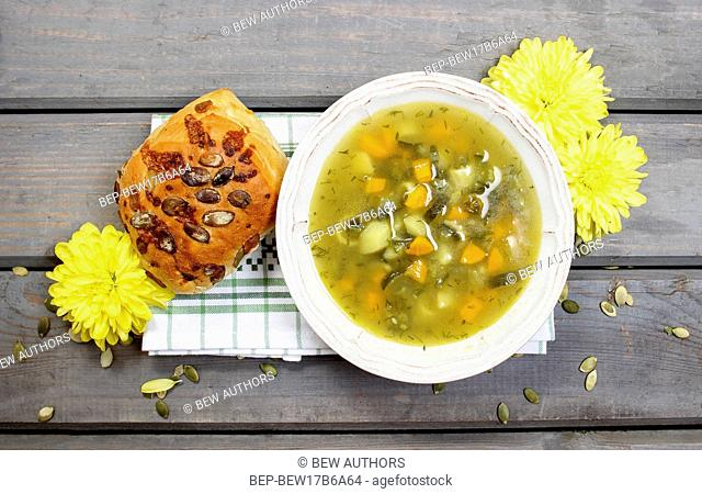 Vegetable soup on wooden table. Basket with fresh bread in the background