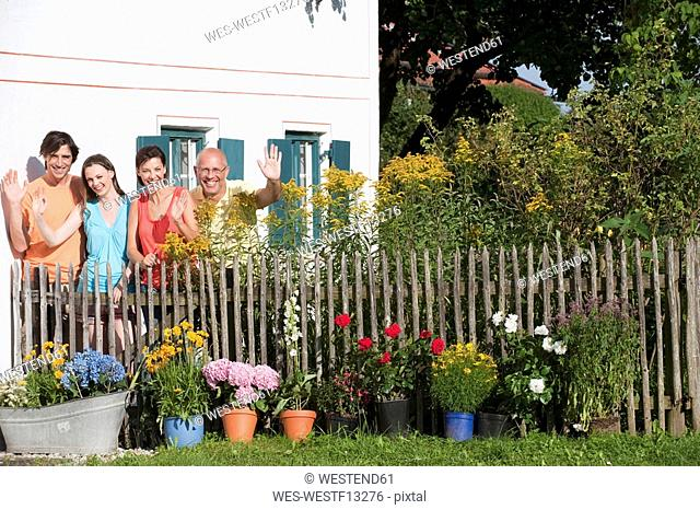 Germany, Bavaria, Four persons standing at garden fence, waving, portrait