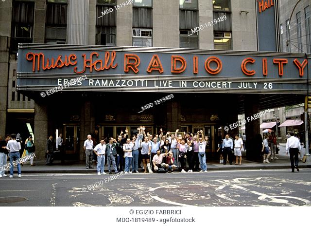 Italian singer-songwriter Eros Ramazzotti posing with some fans outside the New York Radio City Music Hall where he will sing that night