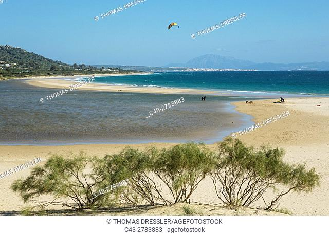 Sandy beaches with kitesurfer at the Bay of Valdevaqueros. In the background the town of Tarifa and the Rif Mountains in Morocco
