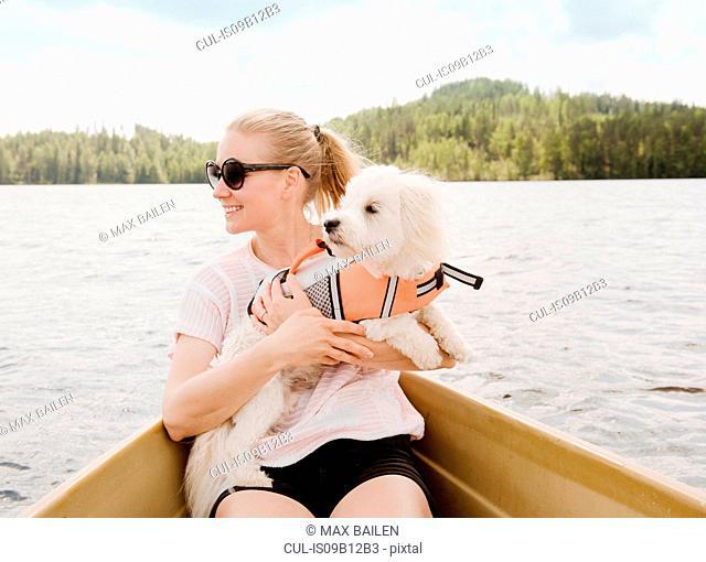 Woman holding coton de tulear dog in boat, Orivesi, Finland
