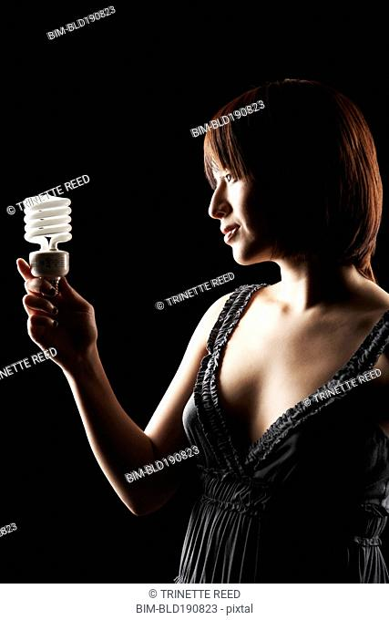 Hispanic woman holding energy efficient light bulb