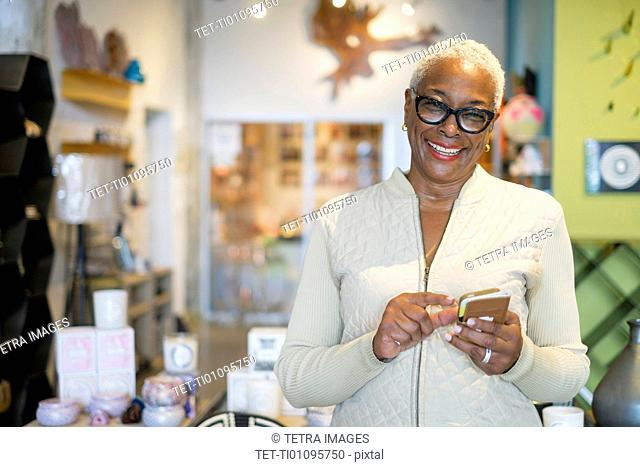 Portrait of woman holding mobile phone in shop