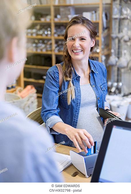 Laughing female customer using credit card machine at store checkout counter