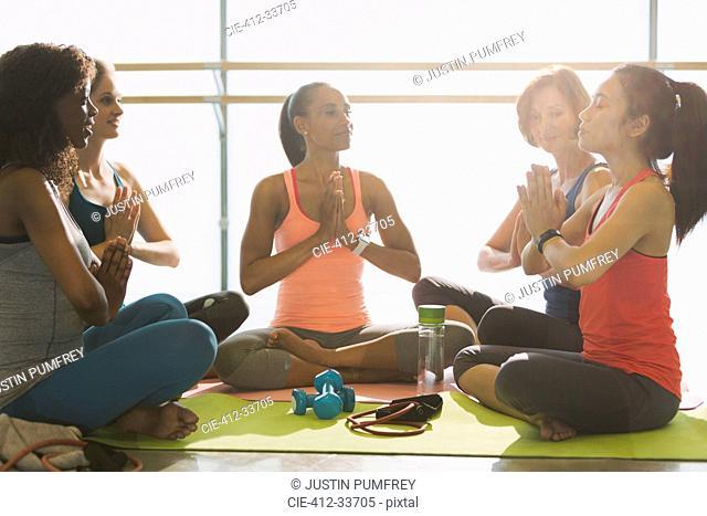 Serene women meditating in yoga class gym studio