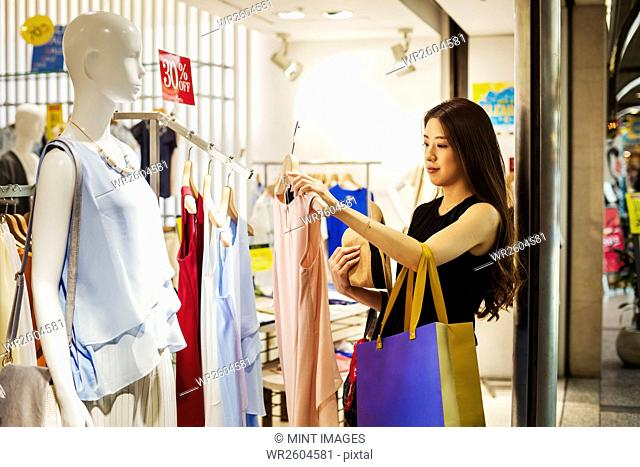Smiling young woman with long brown hair in a clothes shop