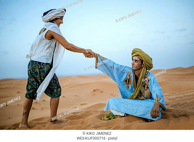 Woman helping her Berber guide to get up from the ground