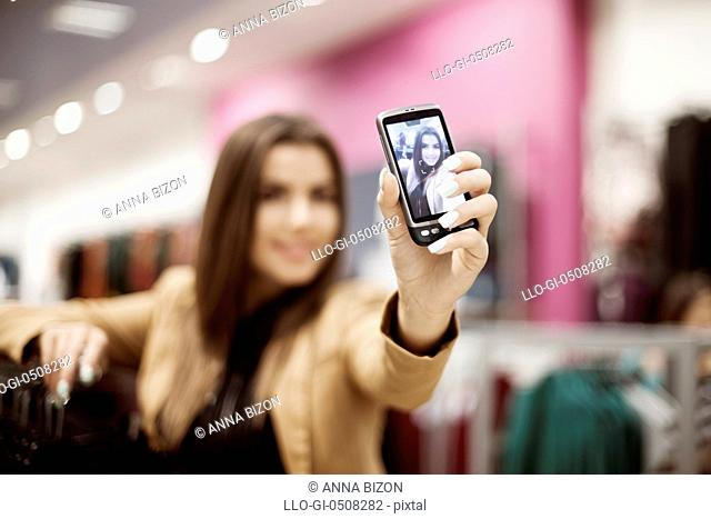 Woman taking self portrait photo in shopping mall Debica, Poland