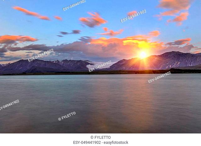 Beautiful dramatic sunset over the incredibly blue lake Tekapo with fog rolling from the mountains. Canterbury region, New Zealand