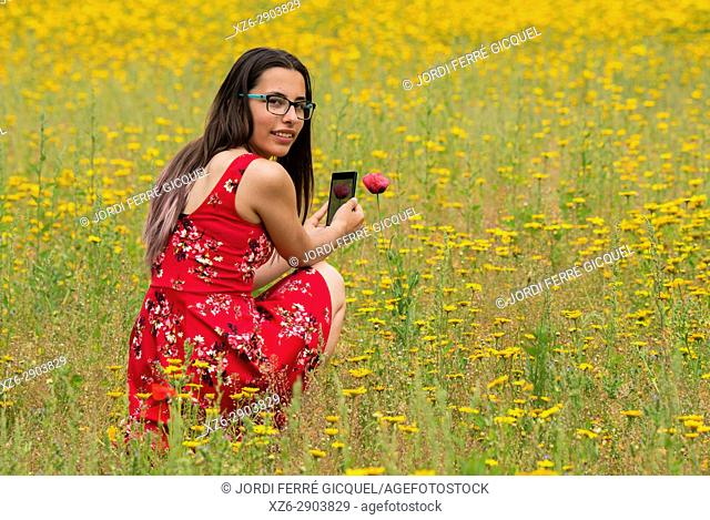 Girl with a red dress taking a photograph to a flower with a mobile in a yellow field
