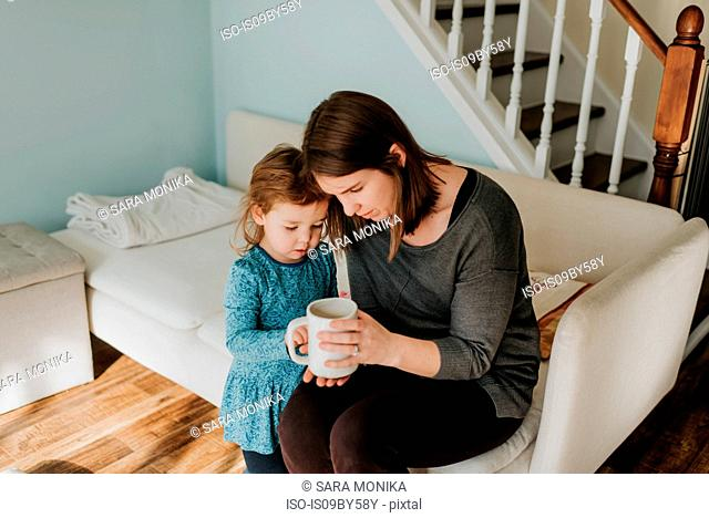 Female toddler and mother looking at coffee cup on sofa