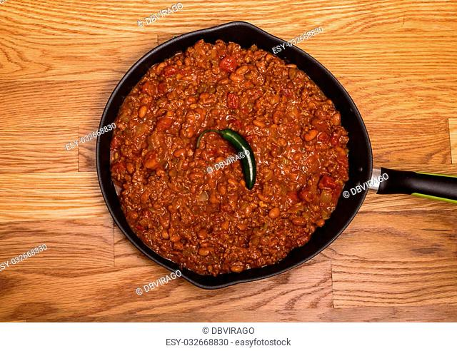 Chili with meat and beans in a black iron skillet on a wood table