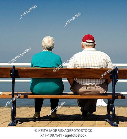 Rear view of an elderly senior couole man woman sitting on seaside bench, summer afternoon, UK