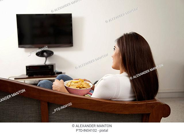 Singapore, Young woman sitting on sofa with bowl of chips