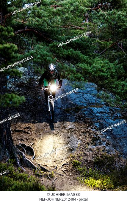 Man cycling through forest