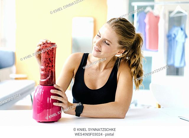 Smiling young woman in sportswear preparing a smoothie