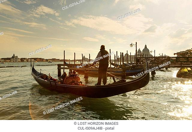 Silhouetted view of gondolier at sunset, Venice, Veneto, Italy