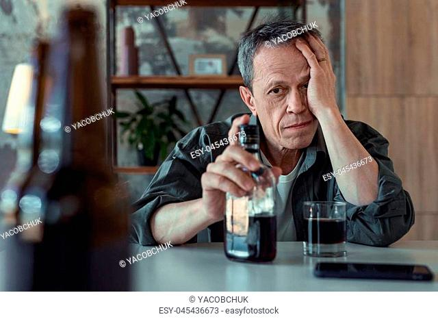 Alcohol addiction. Dark-eyed elderly man drinking bottle of whisky while suffering from strong alcohol addiction