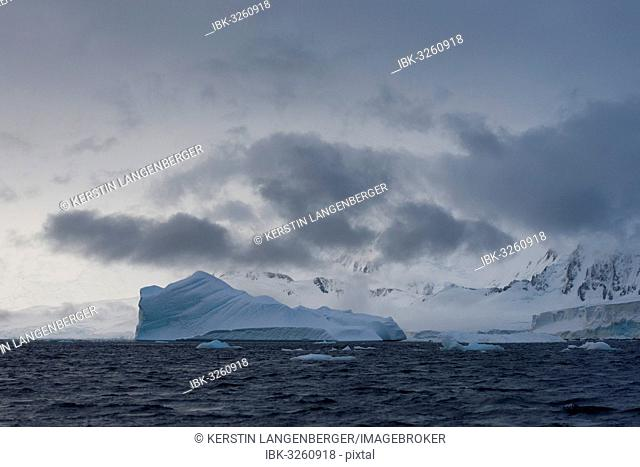 Iceberg in a fjord with mountain scenery and a cloudy sky, Gerlache Strait, Antarctic Peninsula, Antarctica