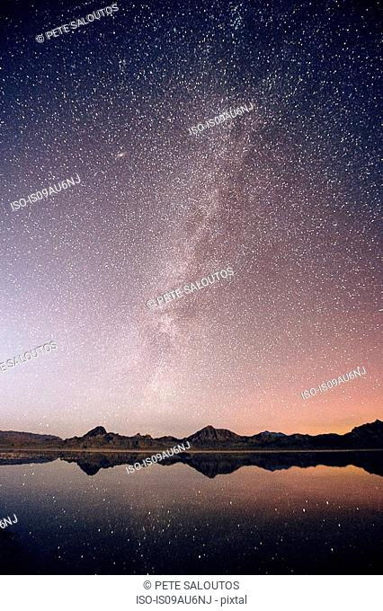 Reflecting pool of mountain range and Milky Way in dramatic night sky, Bonneville, Utah, USA
