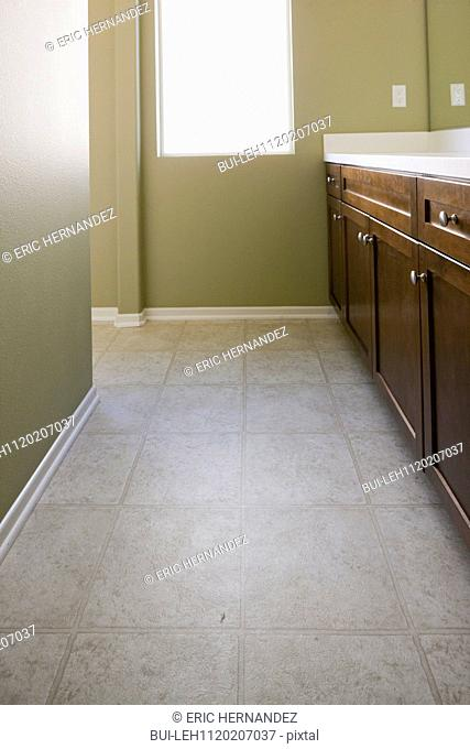 Brown cabinets with tiled floor and light green walls at home
