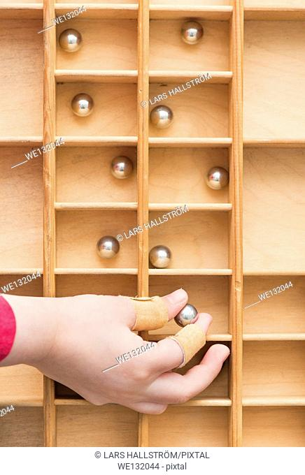 Hand of child placing small steel balls in wooden box with compartments. Conceptual image of organizing, structure and collecting