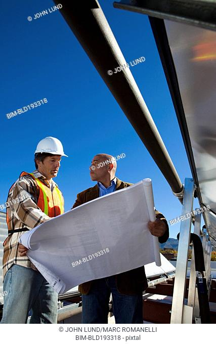 Architect and construction worker on rooftop near solar panels